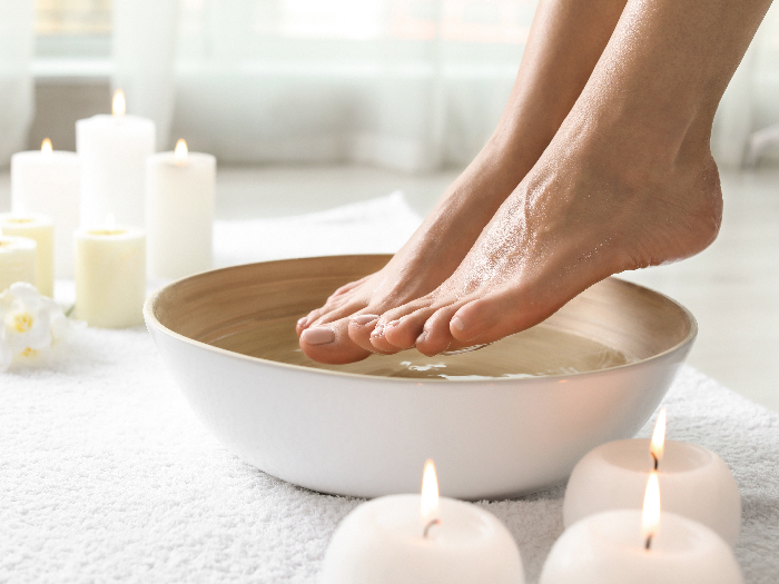 Woman soaking her feet in dish indoors with candles and white towels in the background