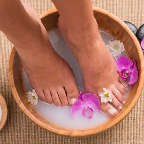Woman soaking her feet in dish with orchids and white flowers in the spa water