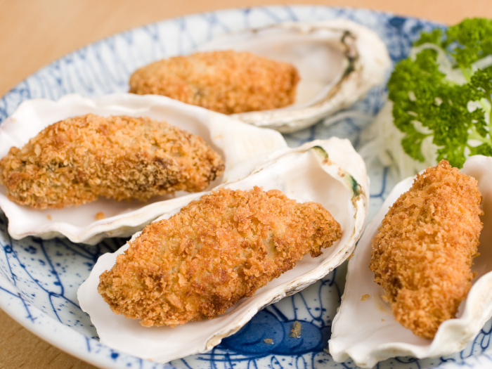 Deep fried breadcrumbed oysters in a half shell.