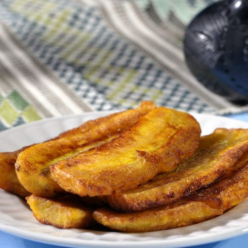Stack of fried sliced plantain bananas on plate