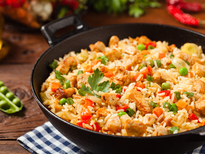 A close up shot of fried rice prepared and served in a wok against a wooden background