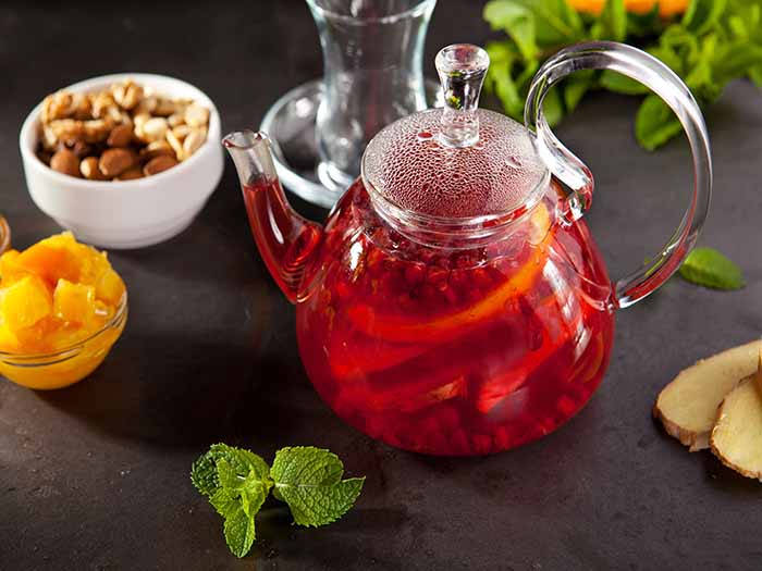 Fruit tea jar surrounded by ingredients