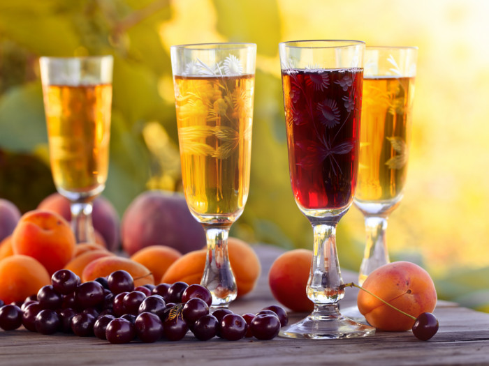 Yellow and red fruit wine in beautiful glasses next to peaches and cranberries