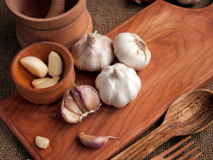 Sliced garlic, garlic clove, garlic bulb in a wooden bowl placed on a chopping board
