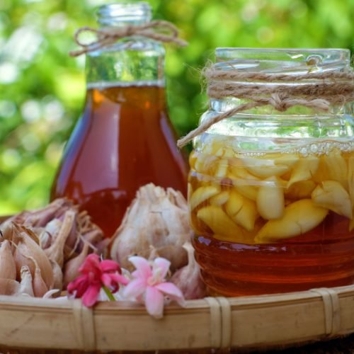 Jars of honey and garlic soaked in honey in a basket with garlic and flowers