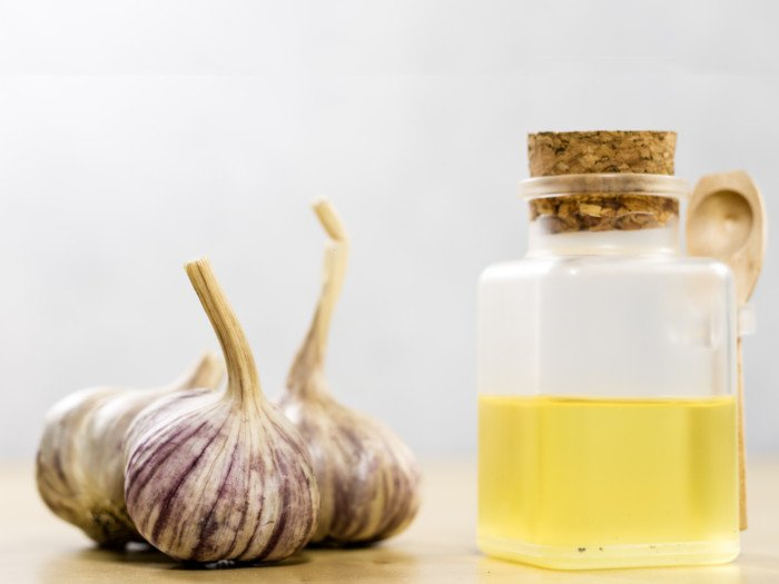 A jar of garlic juice with whole garlic on a wooden table