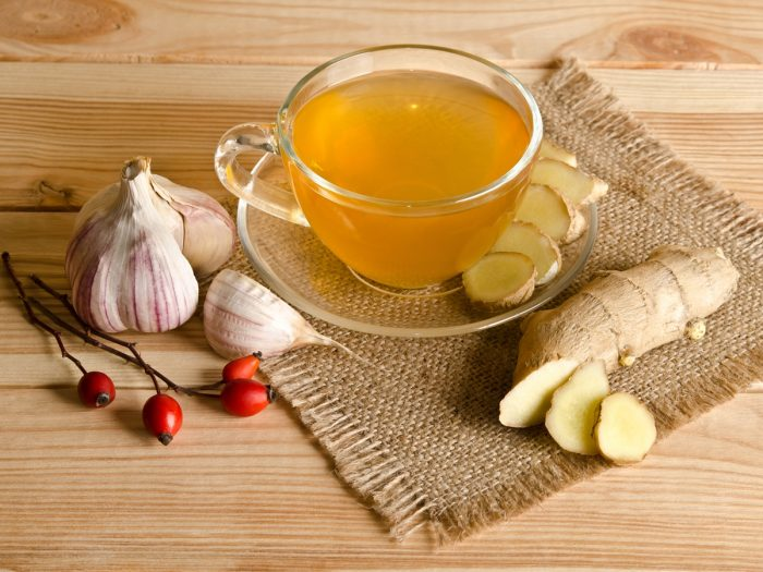 A cup of garlic ginger tea, red cherries, and halved and sliced garlic and ginger on a wooden table