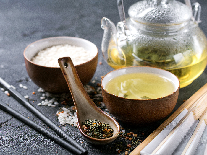Genmaicha tea with roasted brown rice served in the glass teapot and ceramic bowl
