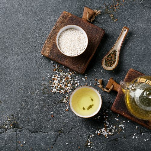 Genmaicha tea in the glass teapot and ceramic bowl and decorated with white rice