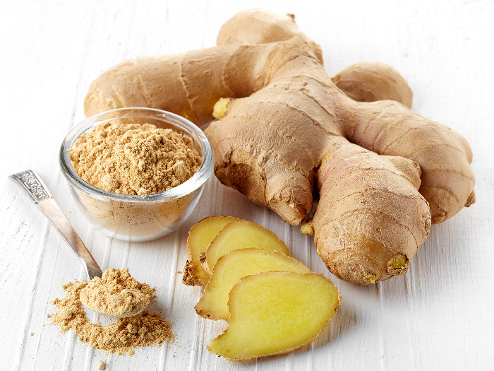 Ginger, sliced ginger, and ginger powder in a glass bowl and spoon