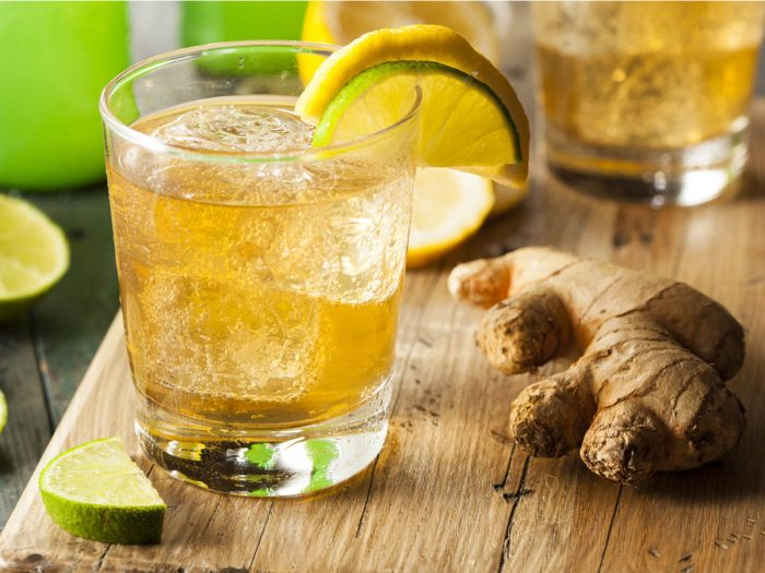A glass filled with ginger ale and a slice of lemon on the rim of the glass