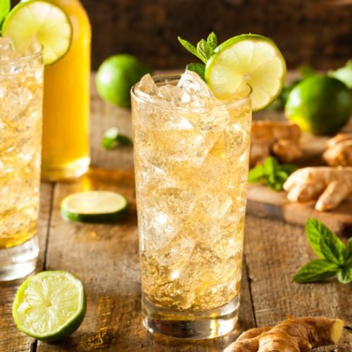 Tall glasses of ginger beer with lime, mint, and ice cubes