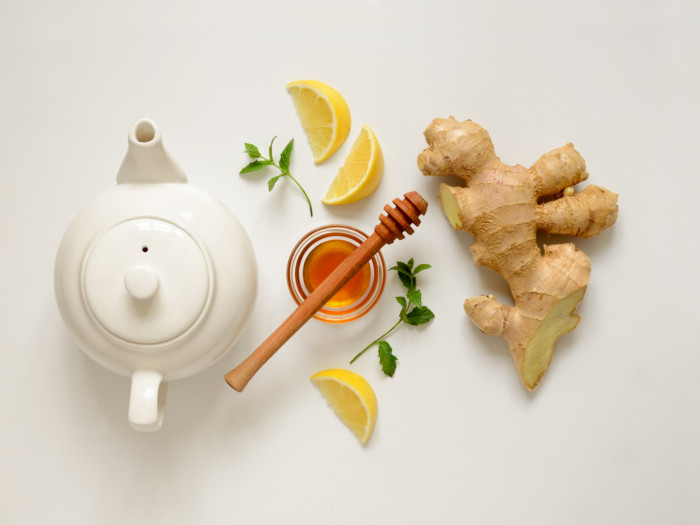 Flatlay picture of a white kettle, honey, lemon, ginger, and mint leaves