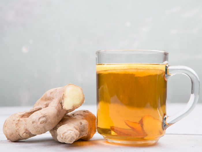 A cup of ginger root tea with halved gingers on a white background