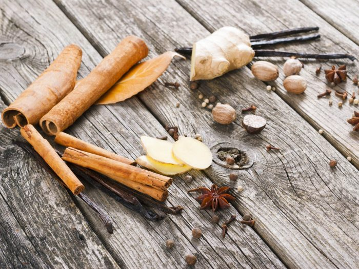 Whole spices like ginger root, sliced ginger, vanilla beans, star anise, and cinnamon sticks on wood