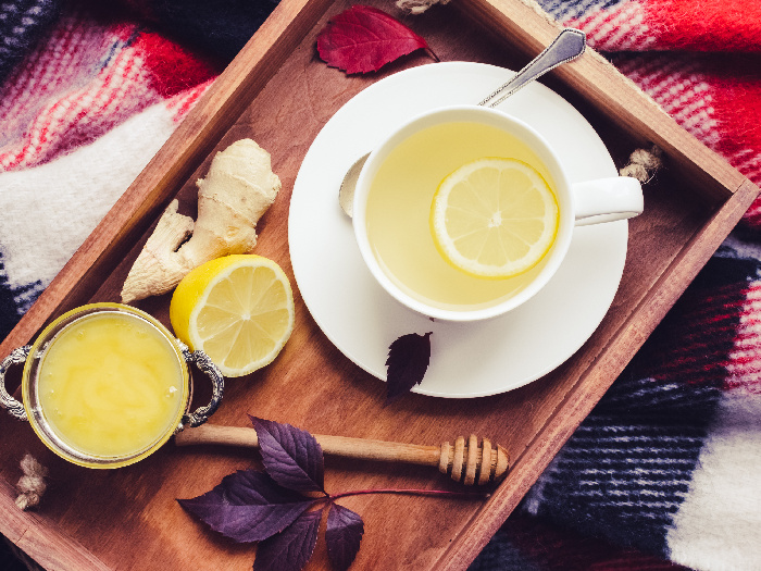 Ginger tea with honey, ginger root and lemon on a wooden tray on a red warm woolen blanket