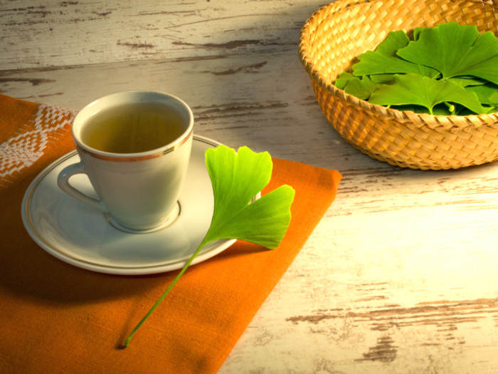 A cup of Ginkgo Biloba Tea kept beside a cane basket filled with fresh Ginkgo Biloba Tea leaves