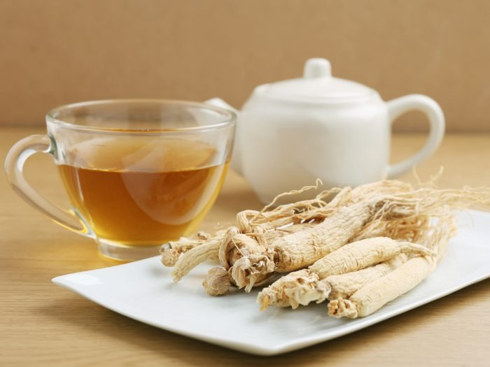 A white cup of ginseng tea, ginseng root, and a kettle on wooden table
