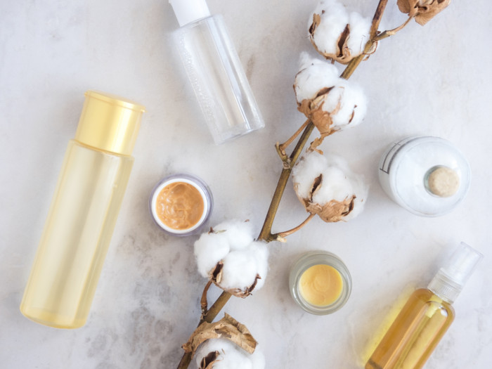 Toner in a bottle, a cotton stalk, and lotions