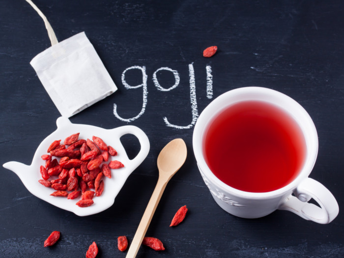 Goji berries on a kettle-shaped plate, a spoon and a cup of tea