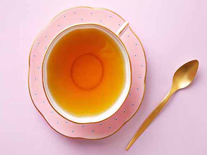 Flatline view of tea in an elegant cup and saucer with a spoon placed alongside