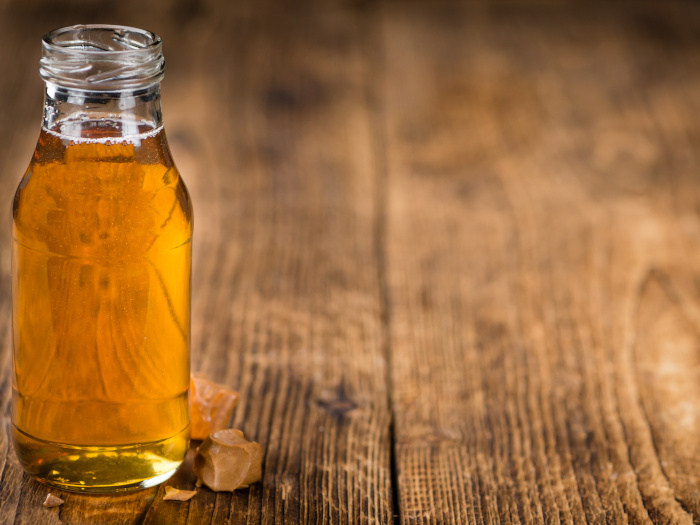 Golden syrup in a glass bottle kept atop a wooden table