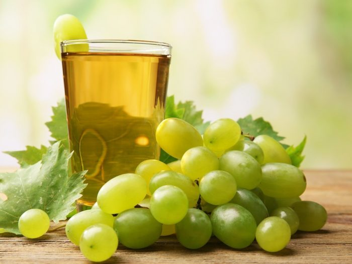 A glass of grape juice kept next to green grapes