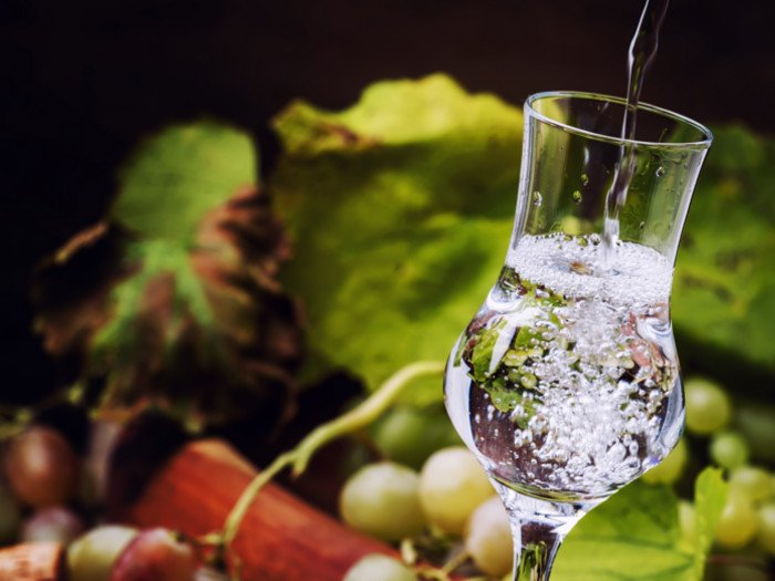 Close up of grappa with grapes in the background