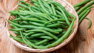 A basket filled with fresh green beans placed on a wooden table