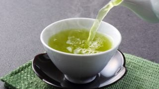 Green tea being poured from a kettle in a white cup that is kept on a green mat