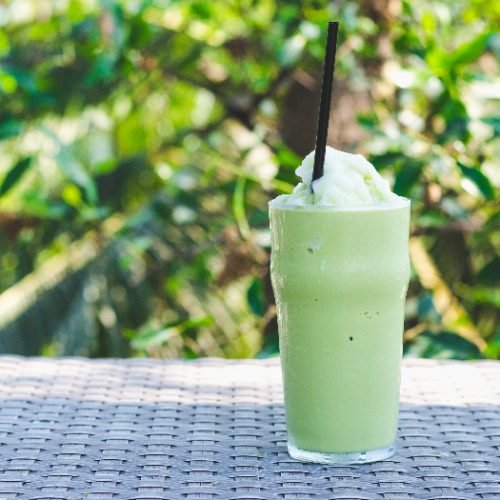 A glass of green tea frappe ice shake with a green plant background