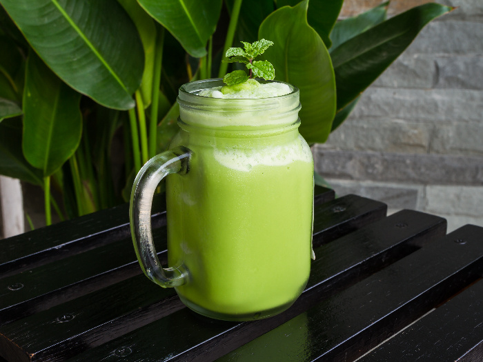 Green tea smoothie in glass on black wooden table