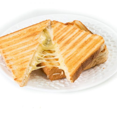 Grilled cheese sandwich on a white plate with cheese oozing out