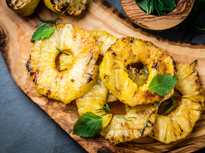 Grilled pineapple slices with fresh mint on a wooden cutting board