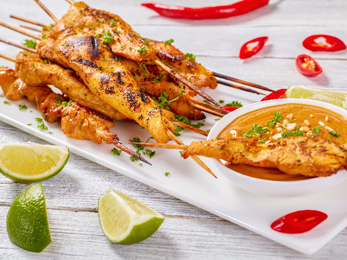 Grilled chicken skewers soaked in flavorful Asian marinade, with a bowl of satay sauce kept on the side as a dip