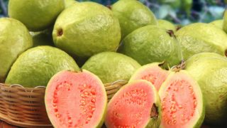 A basket of fresh and ripe guavas with sliced guavas on a wooden table