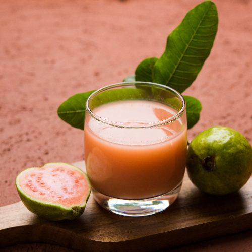 Red guava juice in a glass with a moody background