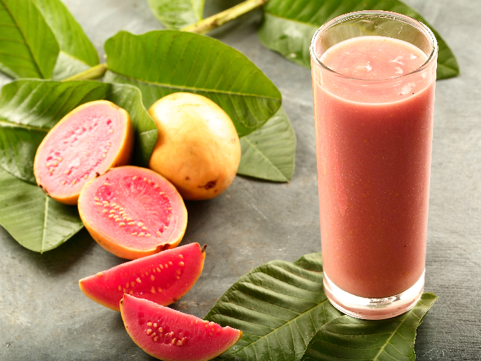 A glass of chilled guava smoothie with organic pink guavas in the background