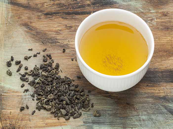 A cup of tea surrounded by gunpowder tea