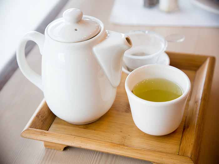 A wooden tray with a teapot and a cup containing gyokuro tea
