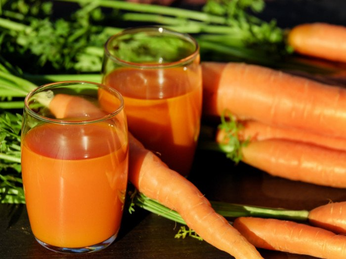 Two glasses of fresh carrot juice kept beside carrots atop a wooden table