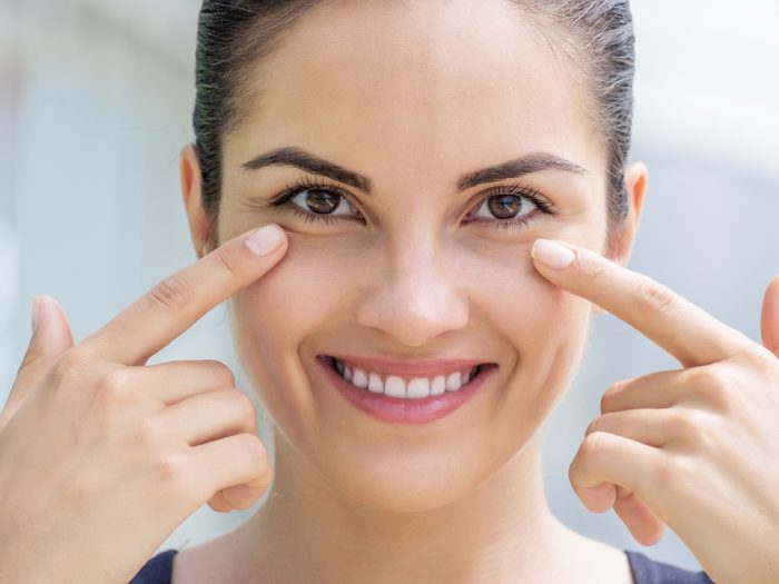 A woman smiling and pointing towards her healthy eyes