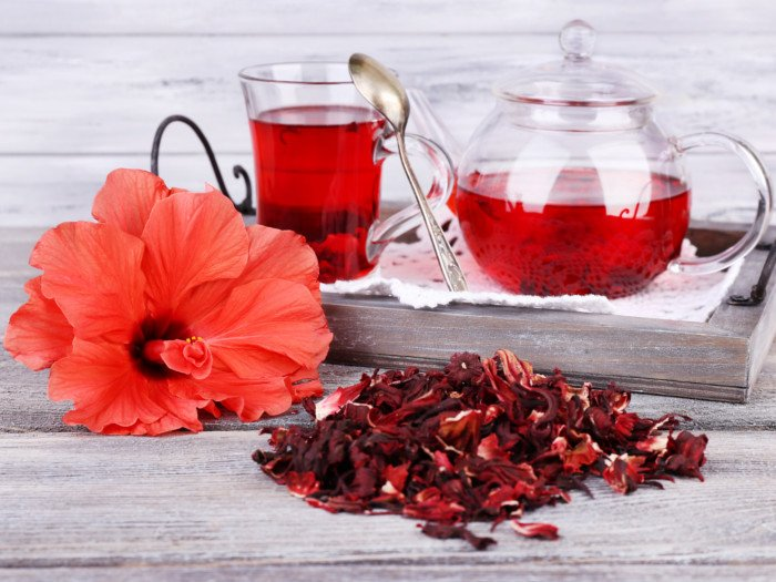 Dried hibiscus leaves and hibiscus tea on a wooden table