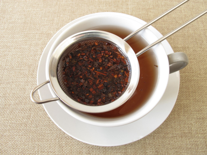 A cup of honey bush tea with a tea strainer on the brim of the cup