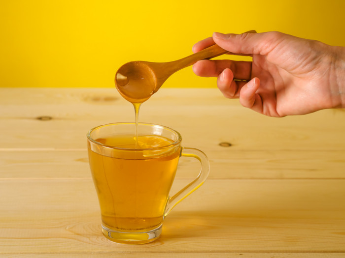 Honey being poured from a wooden spoon into a glass cup of amber liquid containing a citrus slice