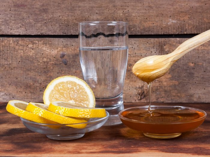A glass of water, flat bowl of sliced citrus fruits, and a bowl of honey on a rustic background.