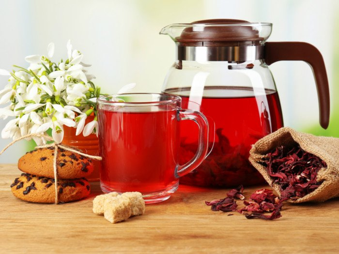 Hibiscus tea in a kettle and a teacup alongside cookies and flowers