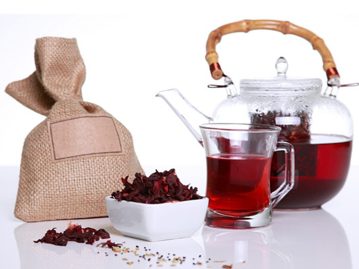 Hibiscus tea in a glass, jar and dried hibiscus flowers on a table