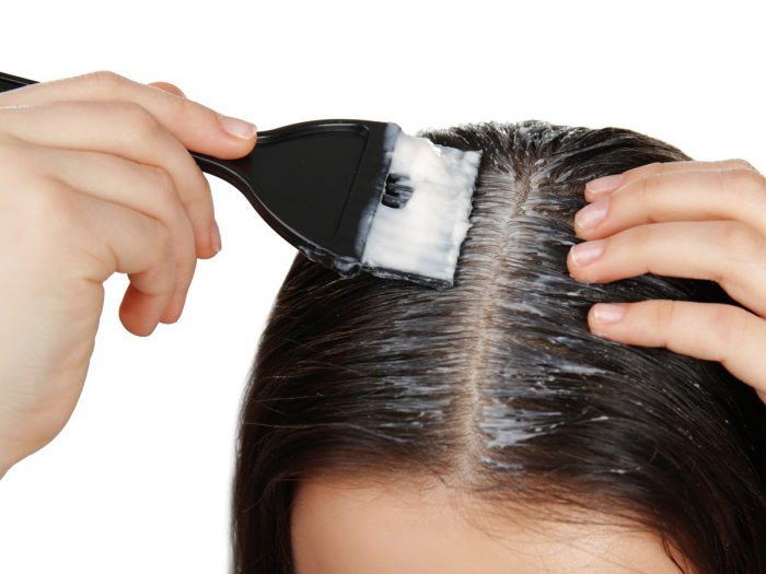 Close up of woman applying coconut oil on her scalp with a brush