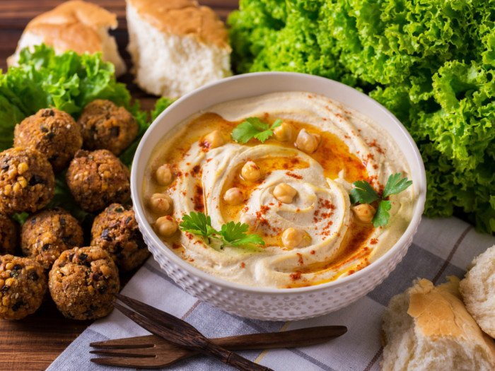 A bowl of hummus, next to salad leaves, falafel, and bread